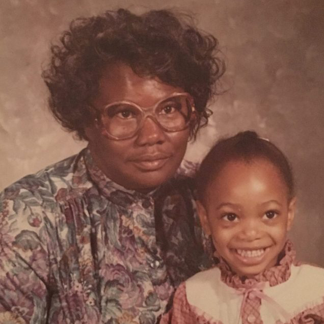 A sepia-colored photo of a Black woman and girl smiling for a portrait against a cloudy brown background. The woman has short, curly black hair and wears brown glasses and a collared shirt with a design of purple flowers. The girl in her lap has braided hair and wears pink shirt with a ruffly white collar and bow.