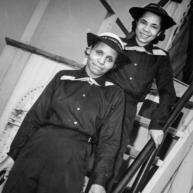 A black-and-white photo of two women, one in front of the other, smiling at the camera on the steps of the ship wearing the U.S. Coast Guard uniform.