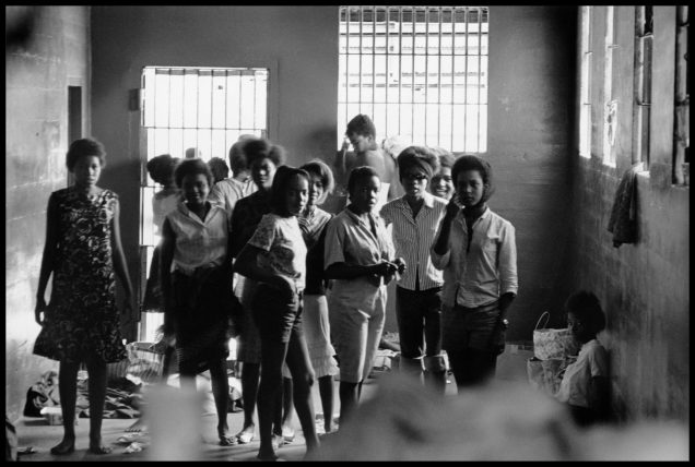 USA. Leesburg, Georgia. August, 1963. Young women are held in the Leesburg Stockade after being arrested for demonstrating in Americus, GA. They have no beds or sanitary facilities. Left to right - Melinda Jones Williams (13), Laura Ruff Saunders (13), Mattie Crittenden Reese, Pearl Brown, Carol Barner Seay (12), Annie Ragin Laster (14), Willie Smith Davis (15), Shirley Green (age 14, later Dr. Shirley Green-Reese), and Billie Jo Thornton Allen (13). Sitting on the floor: Verna Hollis (15).