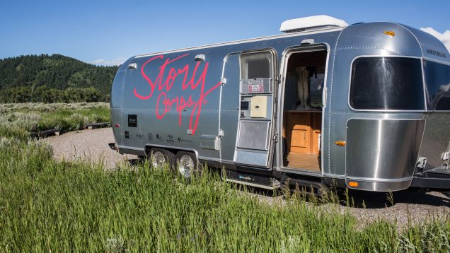 a landscape photograph of a silver airstream trailer with the red StoryCorps logo painted on the side, on a patch of asphalt surrounded by grass in front of a forested hill and bright blue skies. The door to the trailer is open, and some cabinets and recording equipment are visible inside.